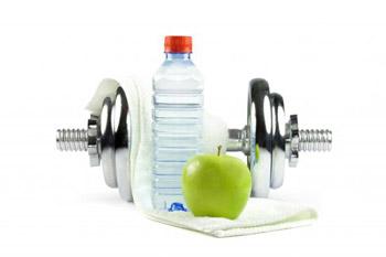 Metallhantel mit Handtuch, Wasser und Apfel (Quelle: Shutterstock/picamaniac)