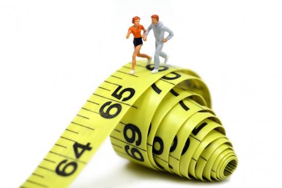 Miniatur-Jogger auf Maßband (Quelle: Shutterstock/Amy Walters)